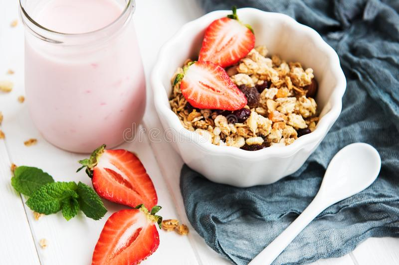 Homemade granola with strawberries. On a white wooden table stock photos