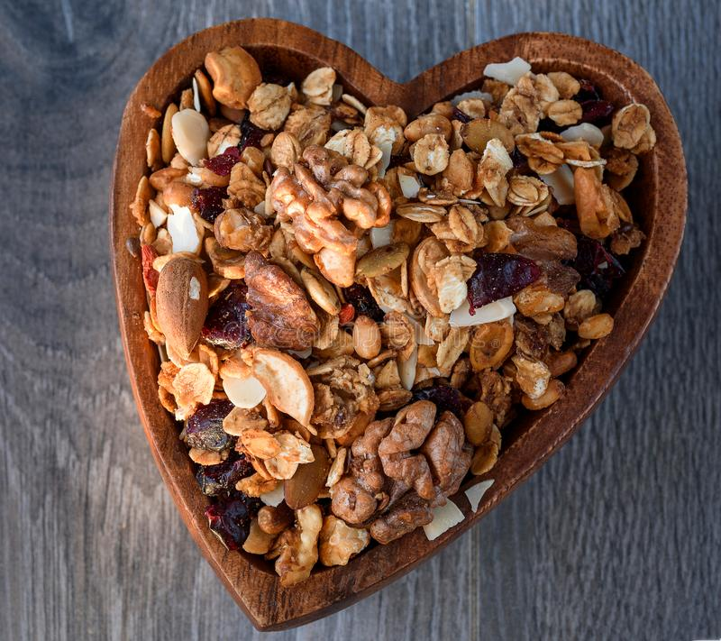 Homemade granola in wooden bowl. Homemade granola in a wooden bowl of heart-shaped royalty free stock photography