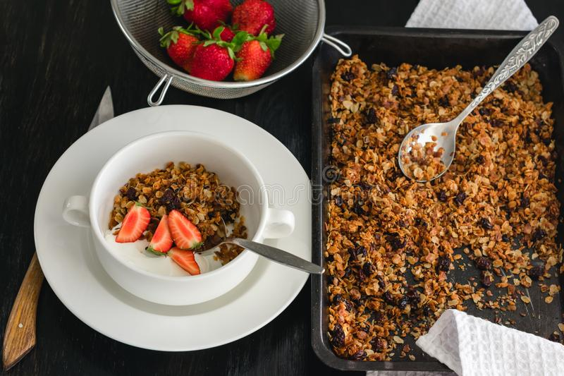 Breakfast of granola, yogurt and strawberries on a dark table. royalty free stock images