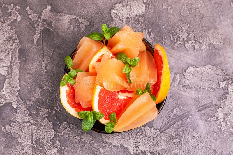 Homemade grapefruit popsicle with ripe grapefruit slices and fresh mint royalty free stock images