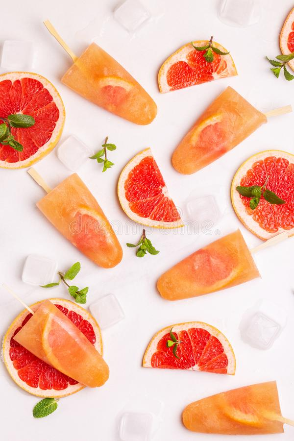 Homemade grapefruit popsicle with ripe grapefruit slices and fresh mint stock photography