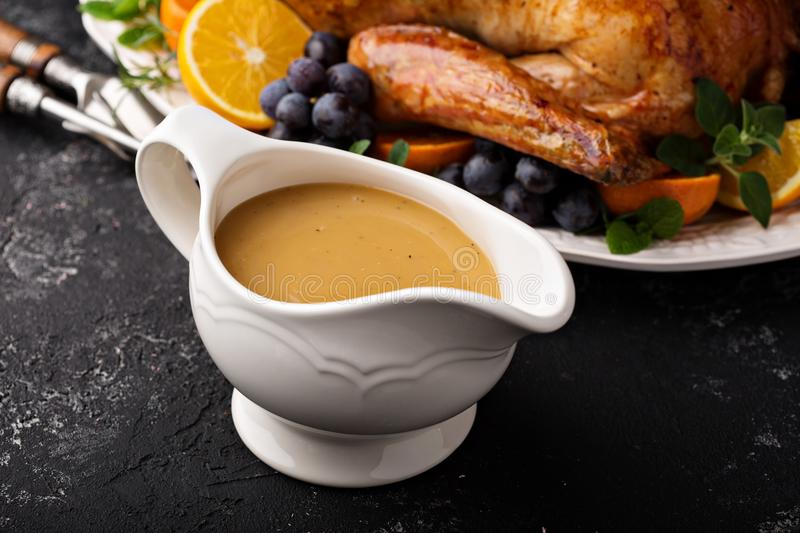 Homemade gravy in a sauce dish with turkey. For Thanksgiving or Christmas royalty free stock image