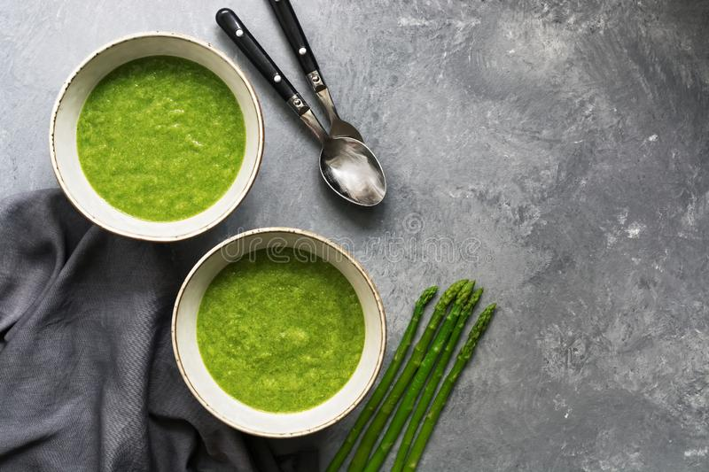 Homemade green cream of asparagus soup on a gray background. Top view,copy space royalty free stock image