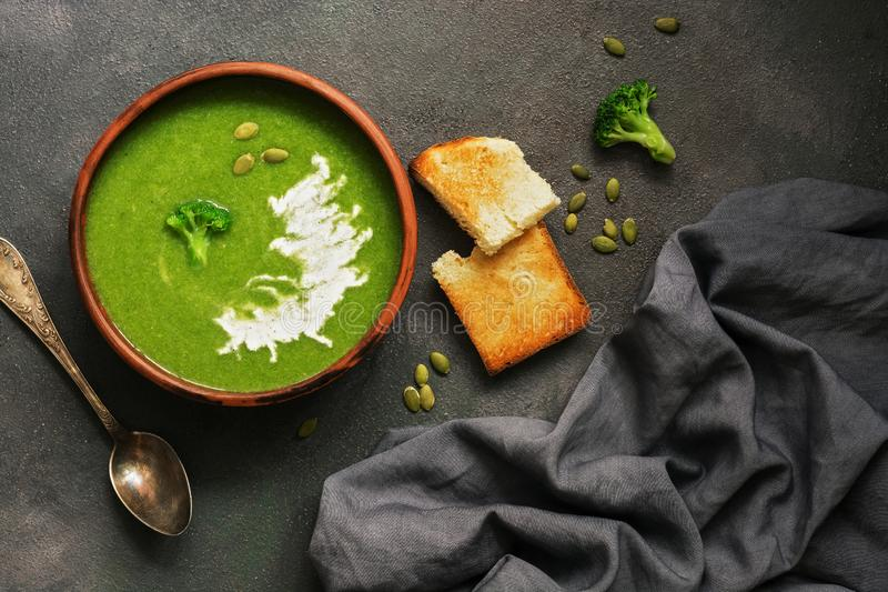 Homemade green cream soup of broccoli with sour cream and pumpkin seeds in a clay bowl on a dark background. Overhead view, flat stock photos