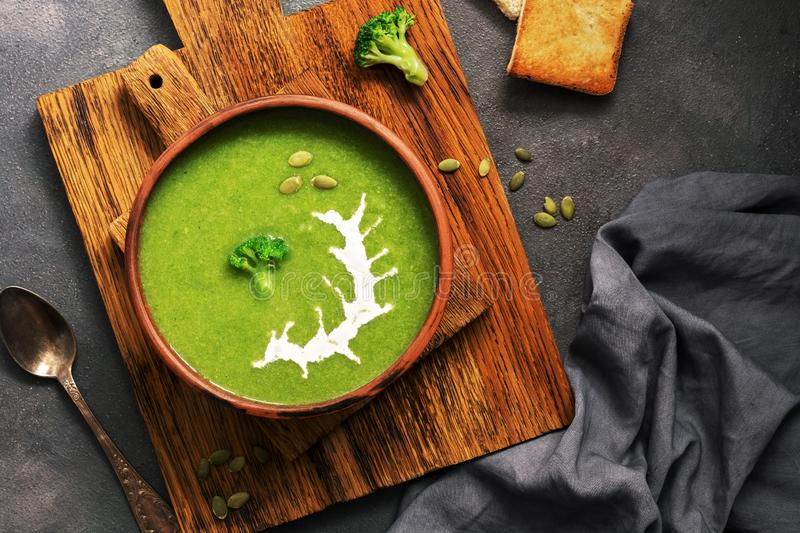 Homemade green cream soup of broccoli with sour cream and pumpkin seeds in a clay bowl on a dark background. Overhead view, flat stock photography