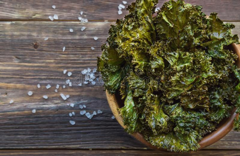 Homemade green kale chips in bowl on rustic wooden background royalty free stock photos