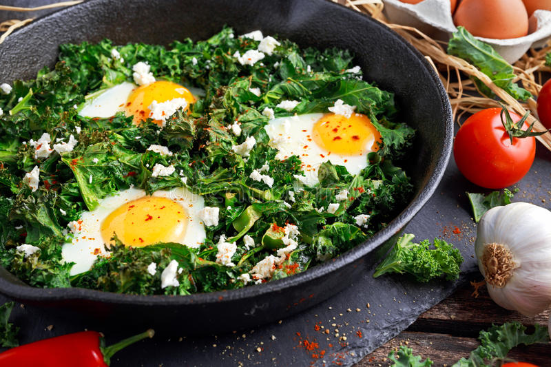 Homemade Green Kale with eggs, feta cheese, herbs in iron pan. healthy rustic breakfast.  royalty free stock photography
