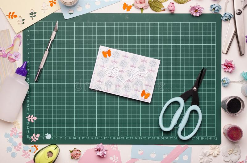 Homemade greeting card and tools on the cutting mat. Scrapbooking, top view royalty free stock photography
