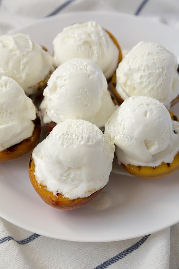 Homemade grilled peaches with vanilla ice cream on a white plate, low angle view. Closeup.  royalty free stock image