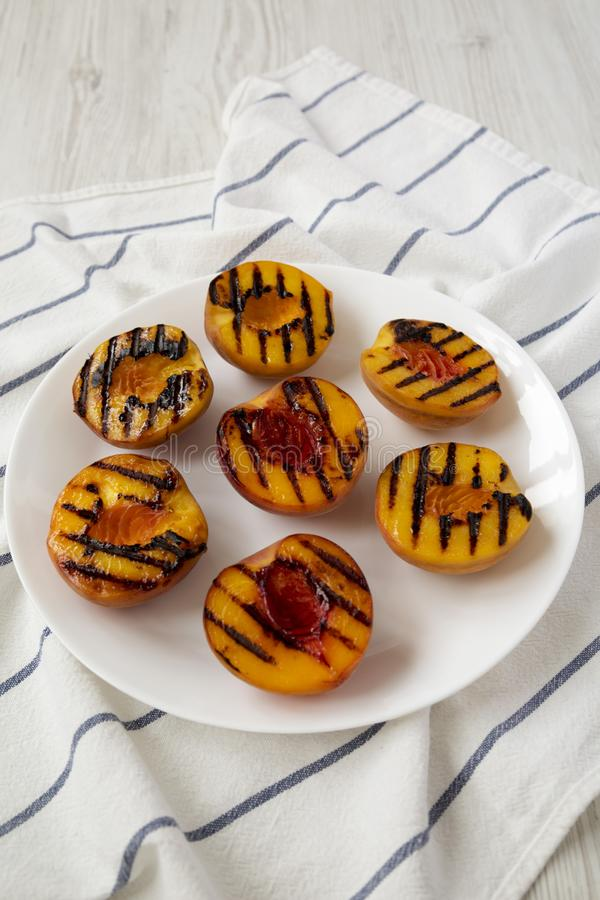 Homemade grilled peaches on a white plate, low angle view. Closeup.  stock image