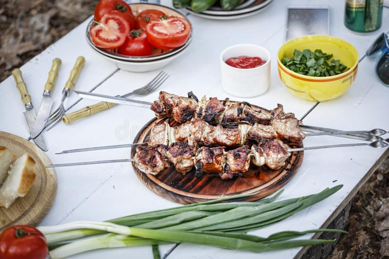 Food, kebab, meat, party, barbeque, eating outdoor, healthy, Concept of outdoor recreation. Homemade grilled skewers with chimichurri sauce served white wooden royalty free stock photos