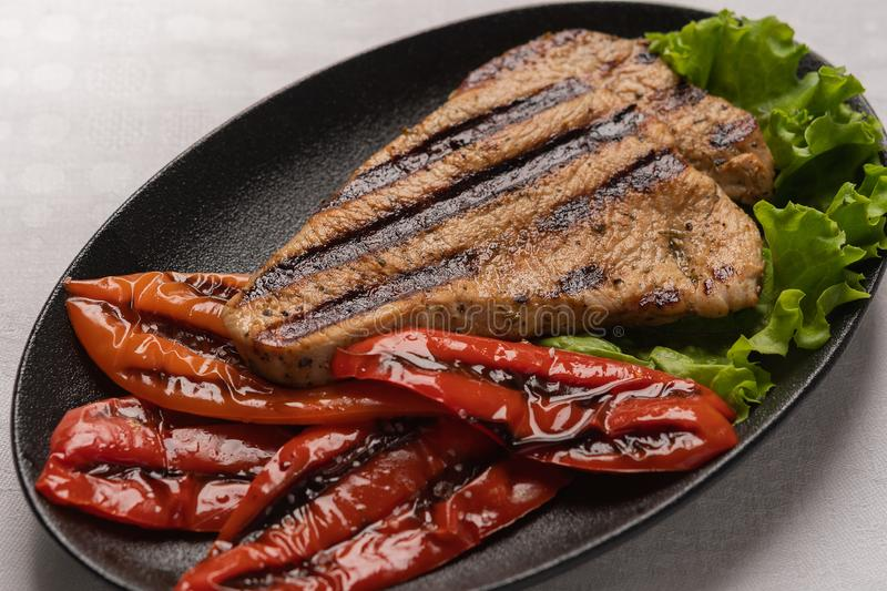 Homemade grilled turkey breast steak with baked peppers and lettuce leaves in a black plate on a light linen background. Grilled turkey breast steak with baked stock photos