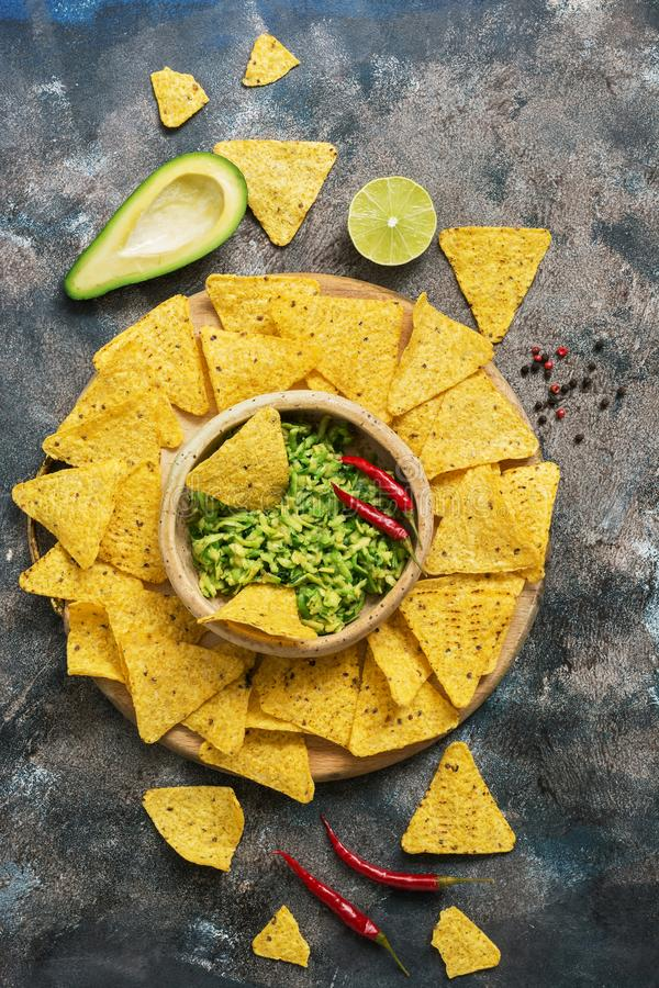 Homemade guacamole with nachos on a rustic background, top view. Mexican food. stock photos