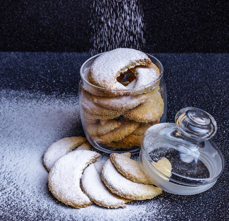 Homemade half-moon shaped cookies in a glass jar with sprinkled stock photo