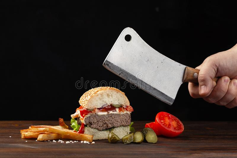 Homemade hamburger cut in half close-up with beef, tomato, lettuce, cheese and french fries on wooden table. Meat cleaver in hand stock photos