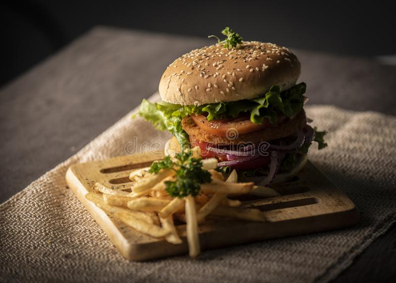 Homemade hamburger over wooden table with dark background royalty free stock photos