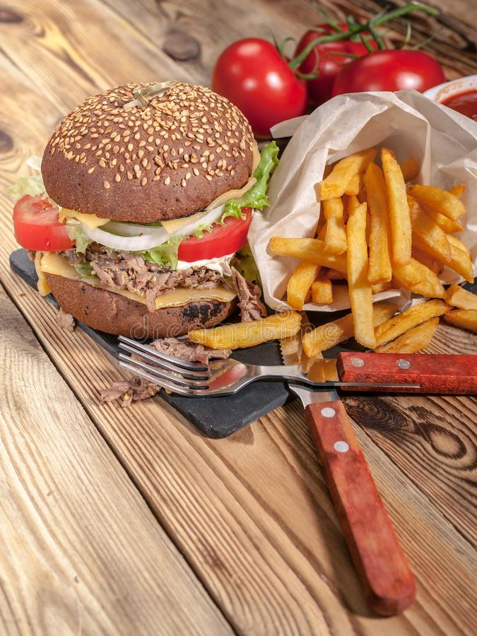 Homemade hamburgers and french fries. Hamburgers with beef, tomatoes, cheese, meat and salad on a wooden table royalty free stock images