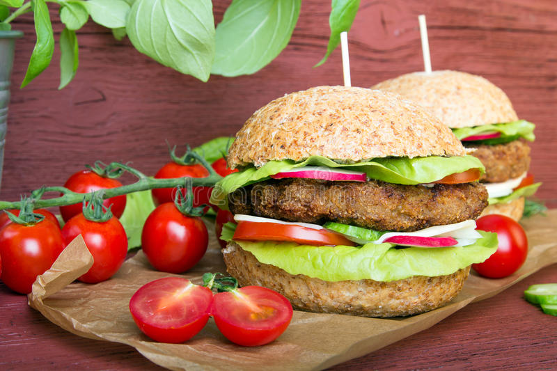 Homemade hamburgers with fresh vegetables. On wooden background royalty free stock image