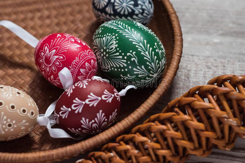 Homemade and handmade Easter eggs on birch branches on wooden tray, traditional czech, Easter egg hunt, whip with ribbons stock image