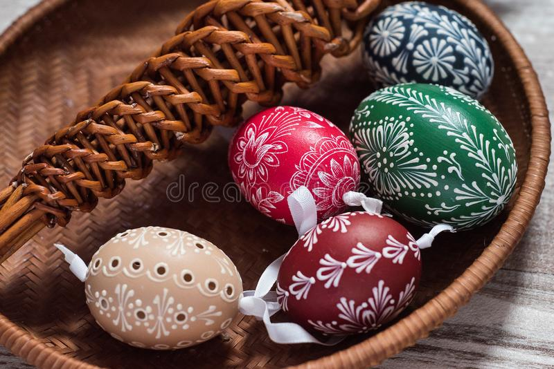 Homemade and handmade Easter eggs on birch branches on wooden tray, traditional czech, Easter egg hunt, whip with ribbons stock photo