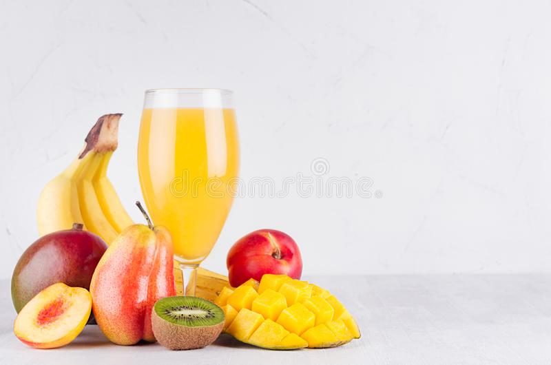 Homemade healthy beverage - multi fruits juice of red, yellow, green, orange fruits on soft light white wood background. stock photo