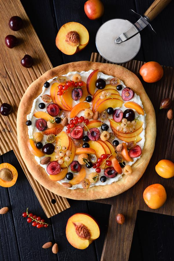 Homemade healthy dessert. Fruit pizza with raw peaches, apricots, cherries, currants and raspberries with ricotta frosting on dark royalty free stock image