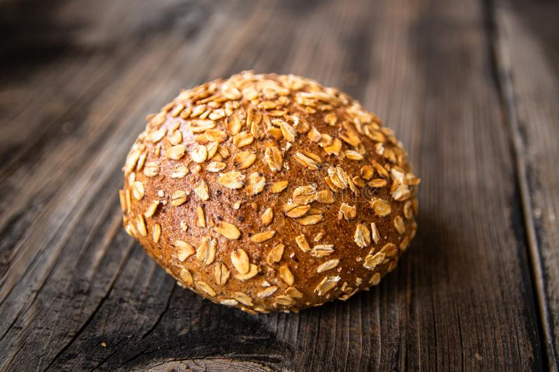 Homemade healthy freshly baked organic whole grain bread with healthy seeds on wooden table stock image