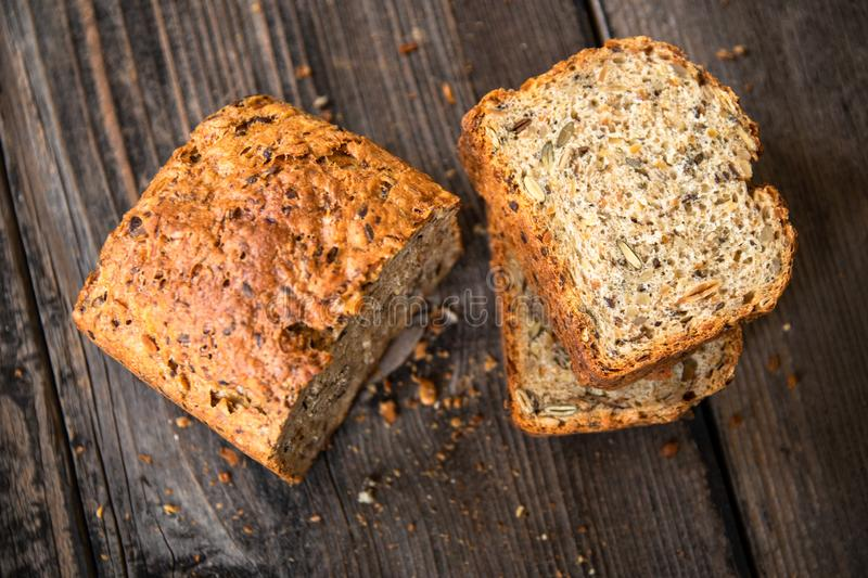 Homemade healthy freshly baked organic whole grain bread with healthy seeds on wooden table royalty free stock image