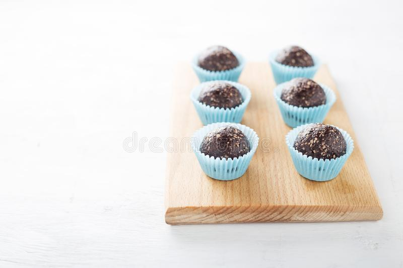 Homemade healthy gluten-free no bake brownie energy bites on cutting board on the white table. royalty free stock photos