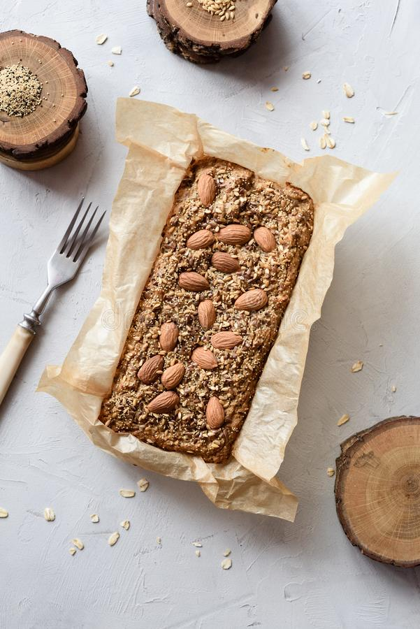 Homemade healthy gluten free pastry. Wholegrain cake with almonds, flax and amaranth seeds in baking paper on gray background top stock image