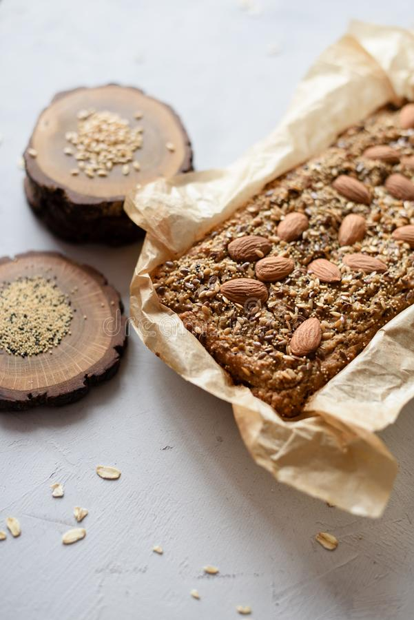 Homemade healthy gluten free sugar free pastry. Wholegrain cake with almonds, flax and amaranth seeds in baking paper on gray stock photography