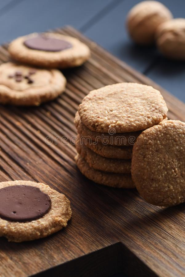 Homemade healthy gluten free sugar free vegetarian sweets. Peanut butter cookies with dark chocolate drops on dark oak board stock photos