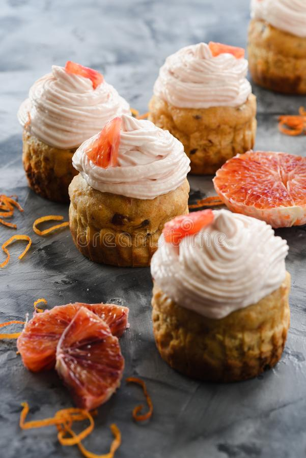 Homemade healthy sugar free sweets. Muffins with cream cheese and blood orange icing on dark background stock images
