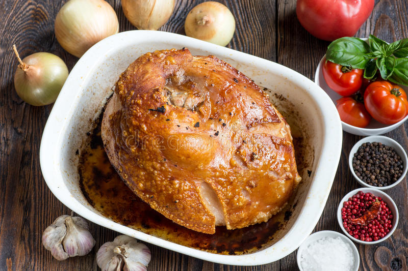 Homemade honey glazed gammon ham with traditional herbs and spic. Gammon with a tomato, garlic, onions and herbs close up on a dark wood background stock photo