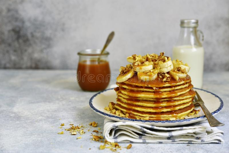 Homemade hot banana pancakes with caramel sauce and nuts. Homemade hot banana pancakes with caramel sauce and nuts on a vintage plate over light slate, stone or royalty free stock images
