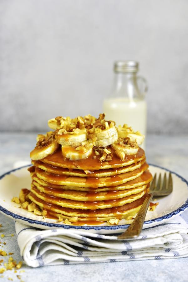 Homemade hot banana pancakes with caramel sauce and nuts. Homemade hot banana pancakes with caramel sauce and nuts on a vintage plate over light slate, stone or stock photos