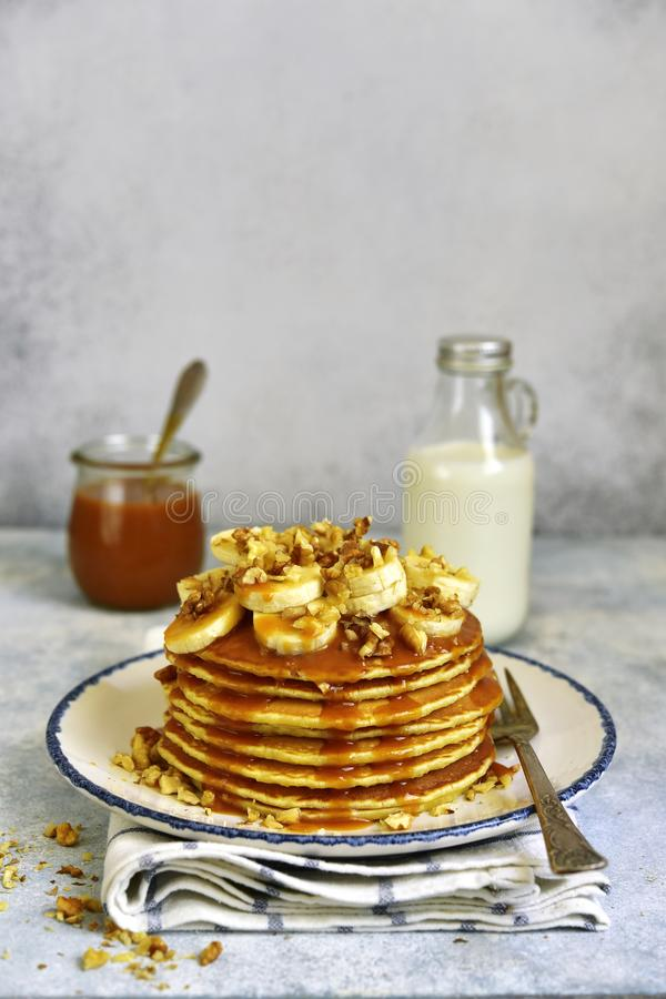 Homemade hot banana pancakes with caramel sauce and nuts. Homemade hot banana pancakes with caramel sauce and nuts on a vintage plate over light slate, stone or royalty free stock image