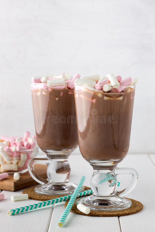 Homemade hot chocolate with marshmallows in glasses. Homemade hot chocolate with marshmallows in glasses on white wooden table stock images