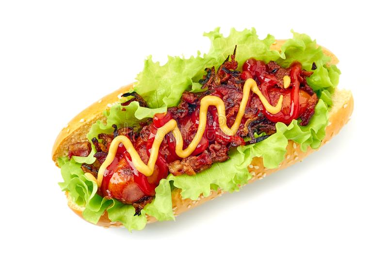 Homemade hot dog on white. Homemade hot dog with lettuce, bacon and onion toppings isolated on white background royalty free stock image