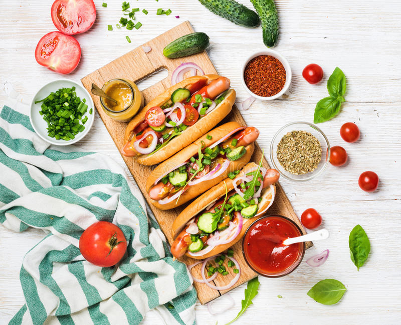 Homemade hot-dogs with fresh vegetables, spices, ketchup and mustard. Homemade hot-dogs on wooden serving board with fresh vegetables, spices, ketchup and royalty free stock photography
