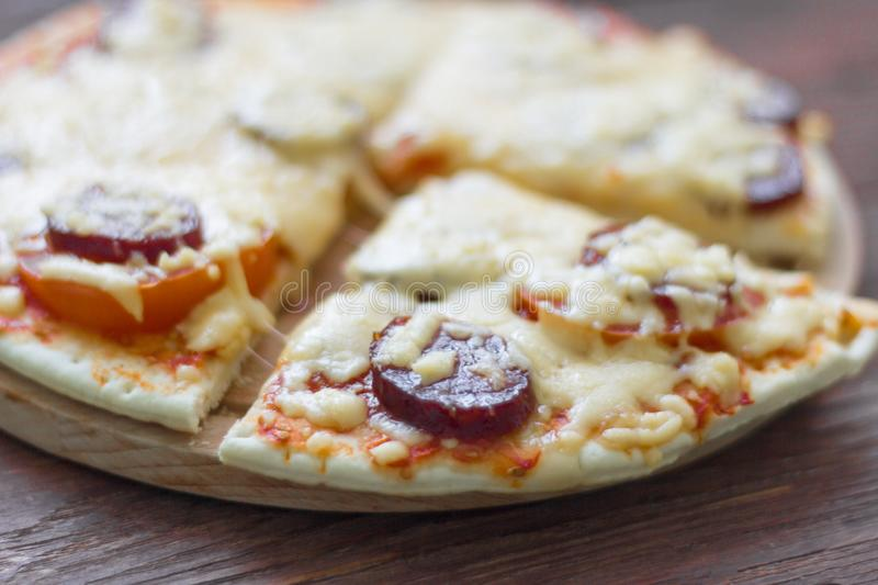 Homemade hot pizza with salami and cheese, pickles and tomatoes on wooden background, ready to eat.  royalty free stock photo