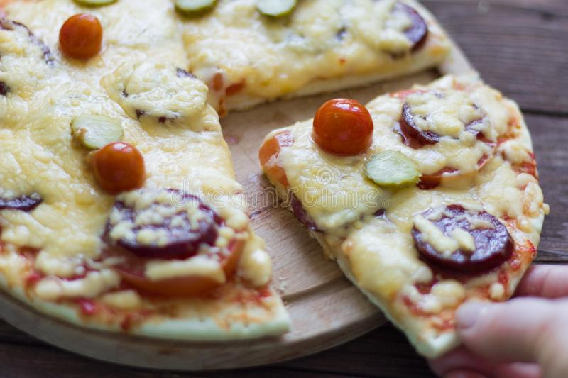 Homemade hot pizza with salami and cheese, pickles and tomatoes on wooden background, ready to eat.  royalty free stock photos