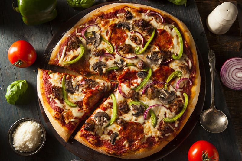 Homemade Hot Supreme PIzza. With Pepperoni Peppers and Sausage royalty free stock photo