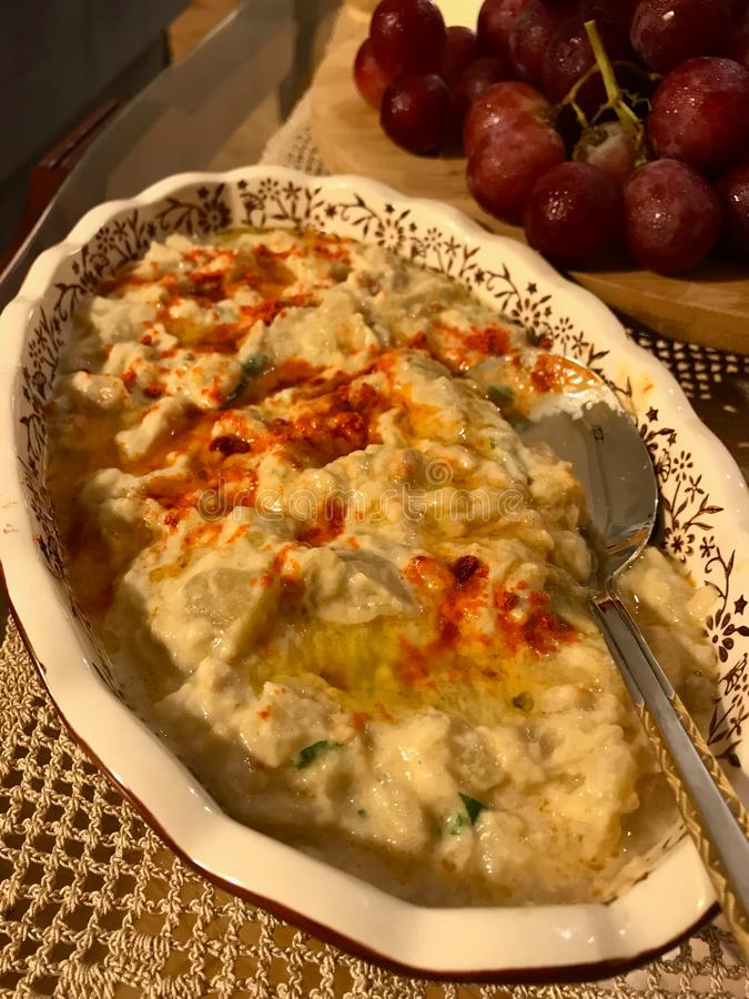 Homemade Hummus with Roasted Aubergine / Eggplant with Fried Butter Sauce and Red Pepper Powder. stock photography