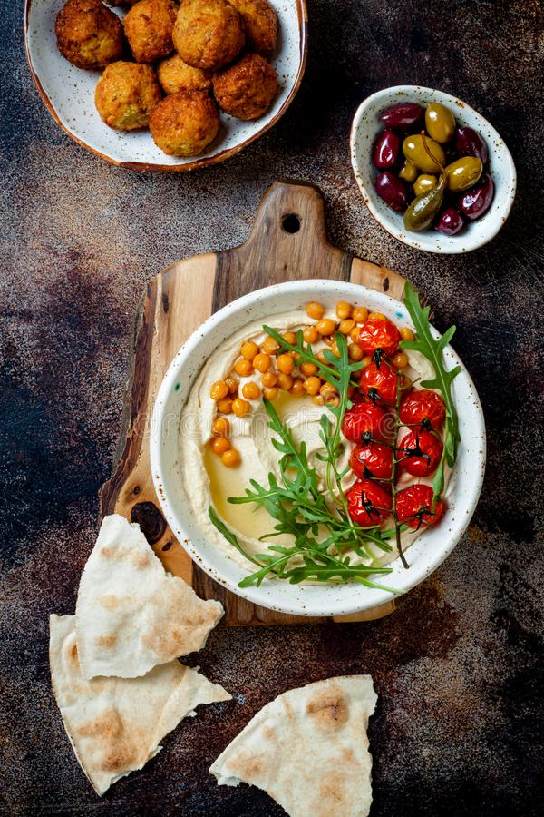 Homemade hummus with roasted cherry tomatoes, falafel balls and olives. stock image
