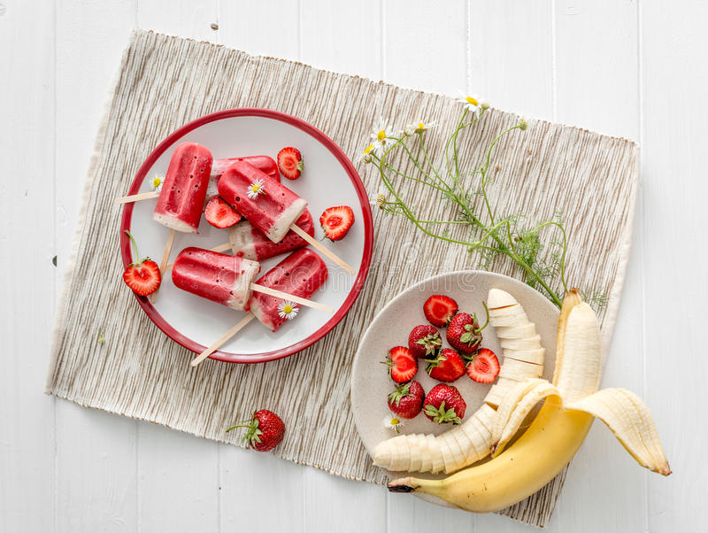 Homemade ice cream from bananas and strawberries, topview. Homemade ice-cream from bananas and strawberries, cut bananas and berries on big white plate, topview royalty free stock image
