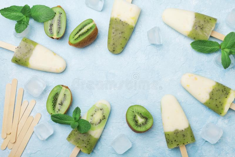 Homemade ice cream or popsicles from kiwi smoothie and yogurt decorated with mint and ice. Top view. Summer sweets stock images