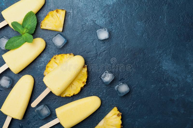 Homemade ice cream or popsicles from pineapple decorated with mint leaf. Top view. Frozen fruit pulp. Summer healthy sweets. royalty free stock photography