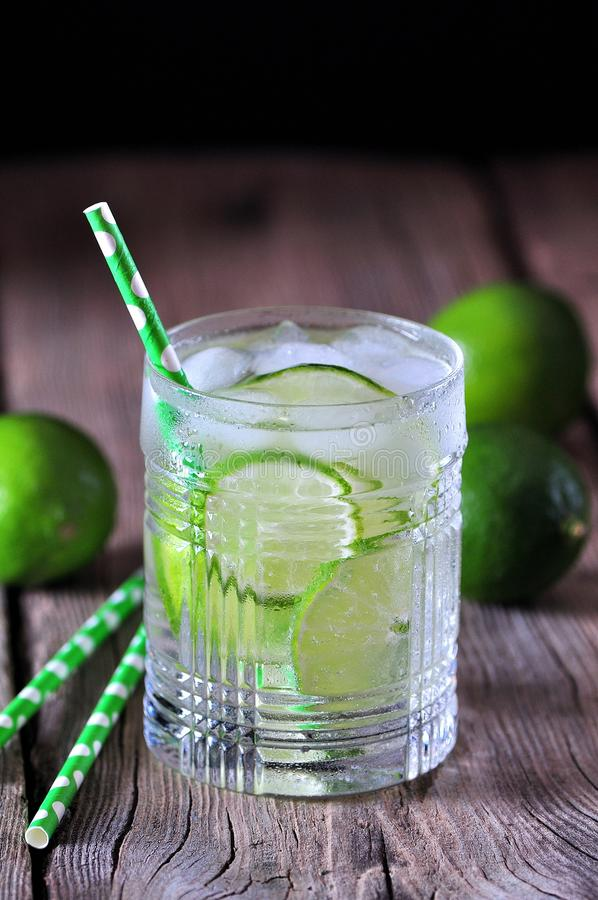 Homemade iced lemonade lime in a crystal glass on the old wooden background. Food royalty free stock images