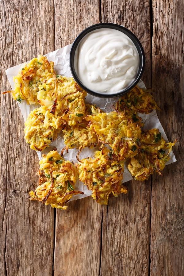 Homemade Indian fried onion bhaji with yogurt close-up. vertical. Homemade Indian fried onion bhaji with yogurt close-up on the table. vertical top view from stock images